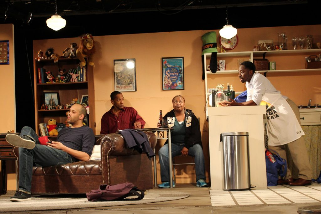 Play set shows a living room with a dining table in the back. A man and a woman sit at the table, another man sits on the couch, and another man leans over a kitchen counter talking