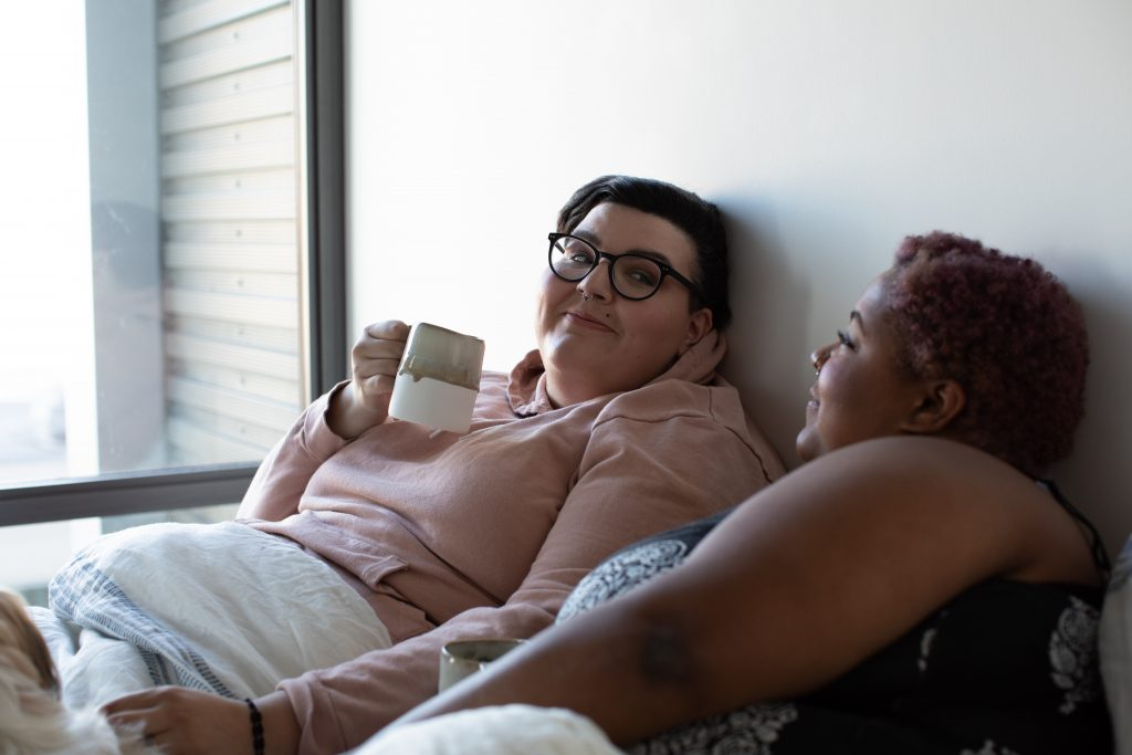 Two female-appearing people in bed with mugs for a column on sex drives