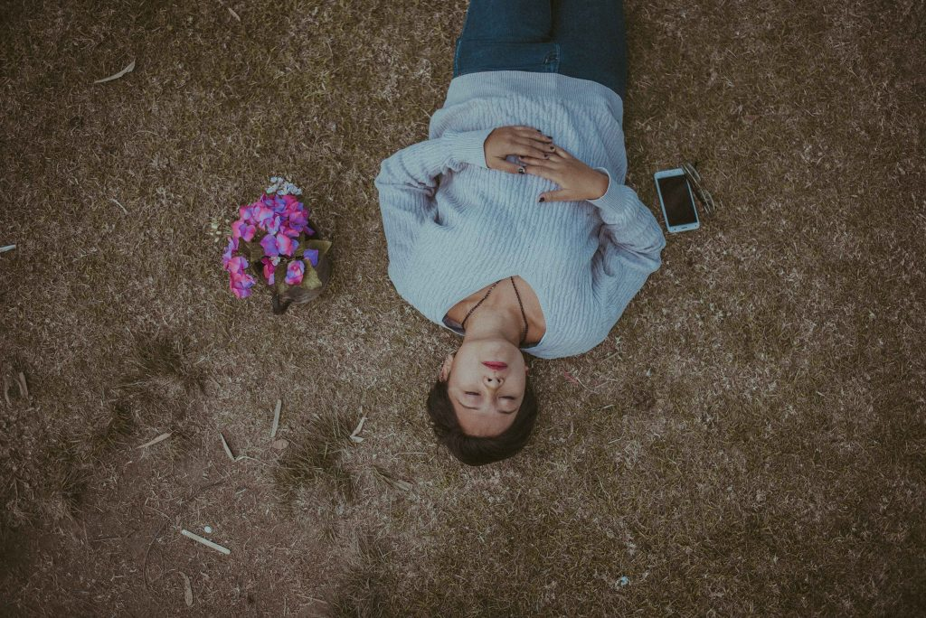 person lying on the ground next to a phone and a bouquet of pink flowers
