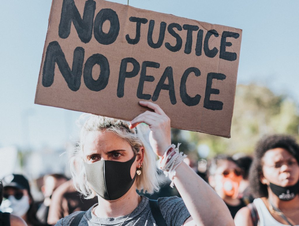 Femme looking person holding a sign saying 'No justice, no peace' for a piece about being an ally
