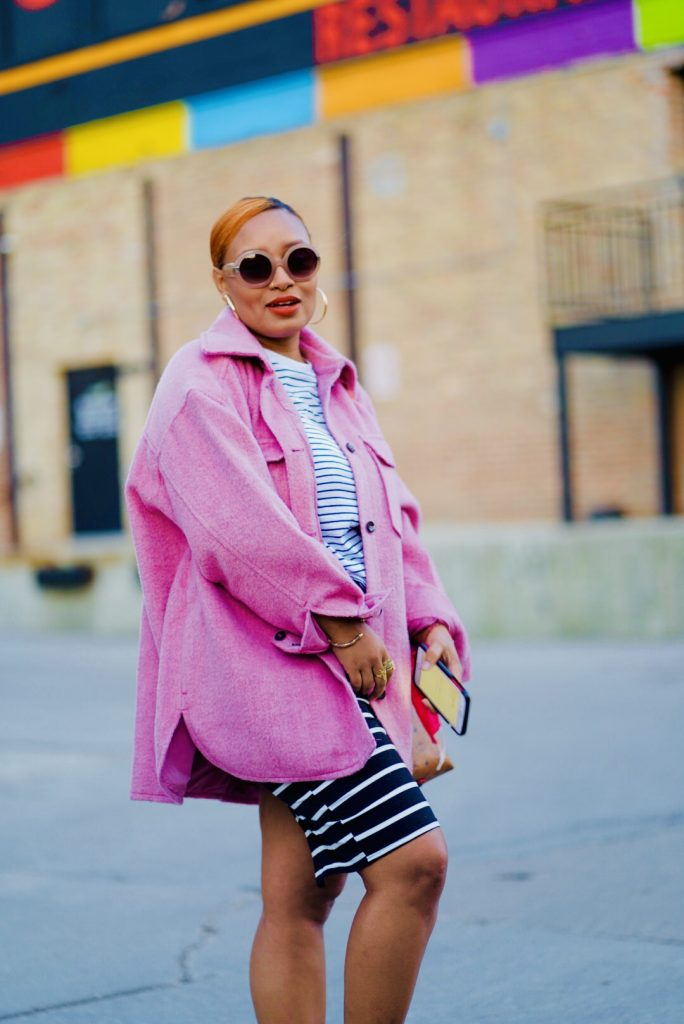 A pregnant Aamina in a pink coat with a black and white pencil skirt